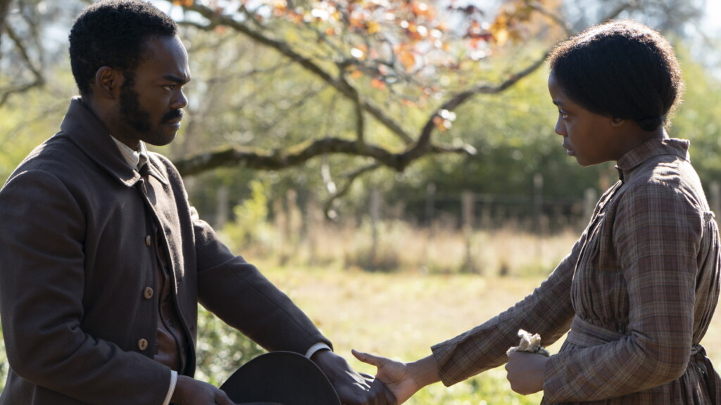 Imagen de la miniserie 'El ferrocarril subterráneo' que muestra a loa personajes de William Jackson Harper y Thuso Mdebu cogiéndose las manos