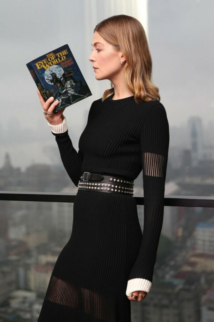 Rosamund Pike, que interpreta a Moraine, la protagonista de La rueda del tiempo sostiene un libro de la saga